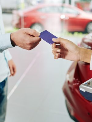 Close-up image of man paying with credit card for rental car